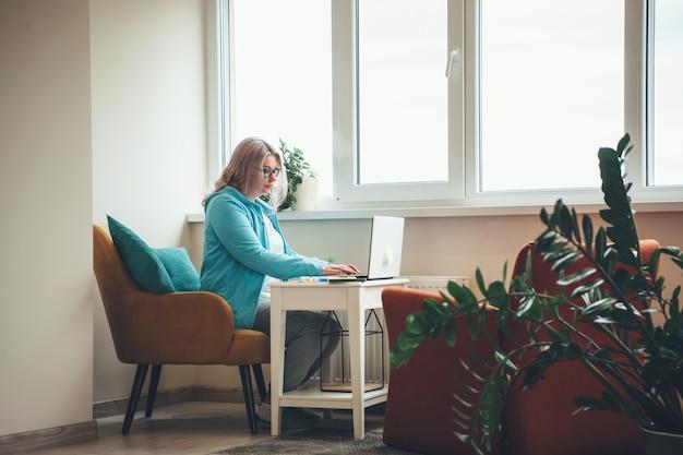 Donna bionda senior concentrata che lavora a distanza al computer portatile durante il blocco