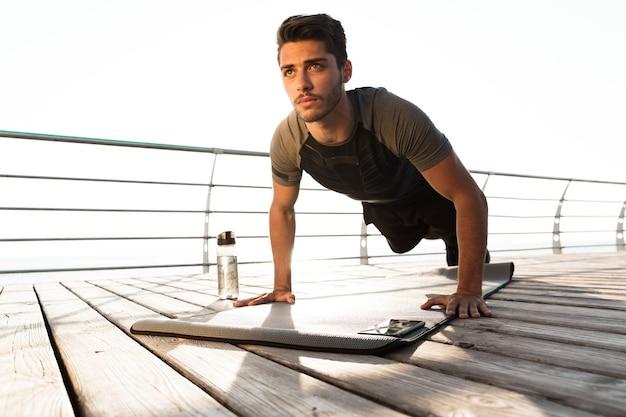 Uomo di sport concentrato all'aperto sulla spiaggia fa esercizi sportivi