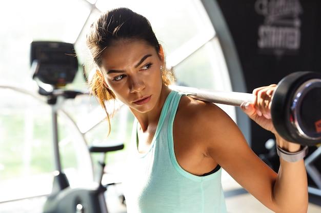 Sportiva concentrata facendo esercizio con bilanciere e guardando lontano in palestra