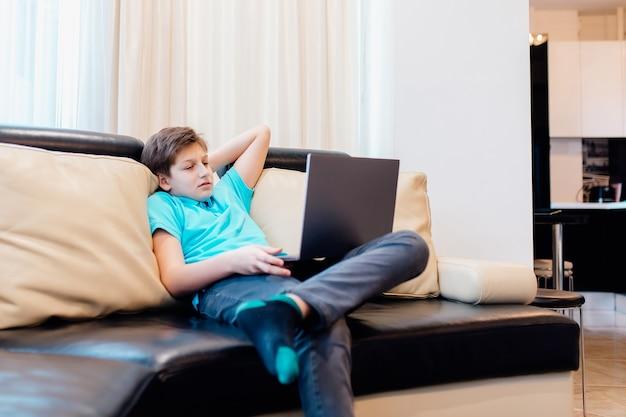 Ragazzo adolescente concentrato seduto sul divano di casa a guardare un film sul computer portatile,