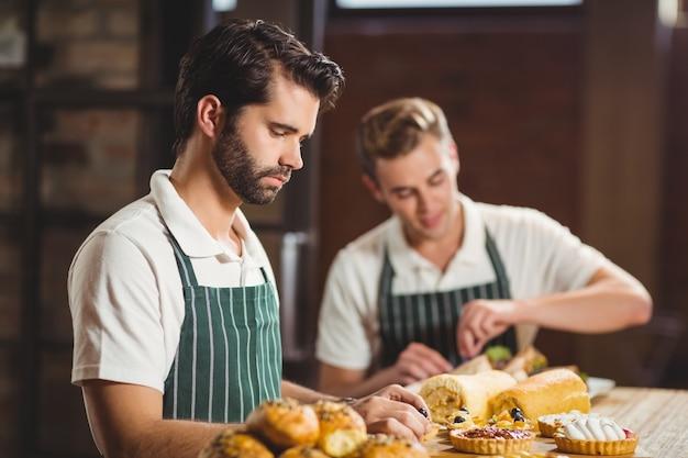 I camerieri concentrati riordina i pasticcini