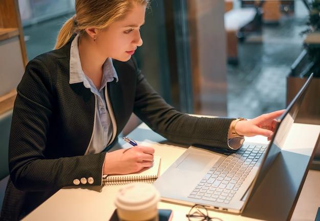 Libero professionista concentrato della donna che rileva le informazioni per il progetto di pianificazione che fa il lavoro a distanza tramite laptop