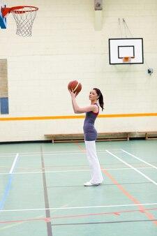 Donna concentrata che pratica pallacanestro