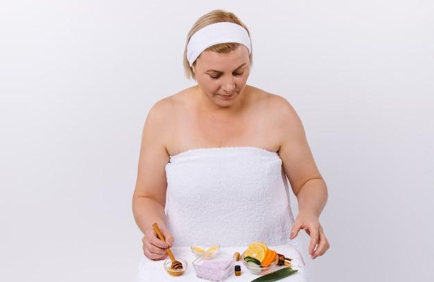 Una donna concentrata con una benda sulla testa e avvolta in un asciugamano fa una maschera a casa con prodotti naturali. foto di alta qualità