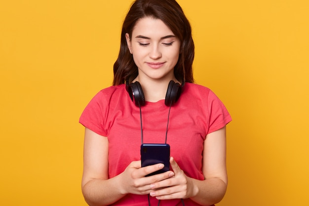 Donna concentrata con capelli scuri che tiene telefono astuto in mano guardando il suo schermo