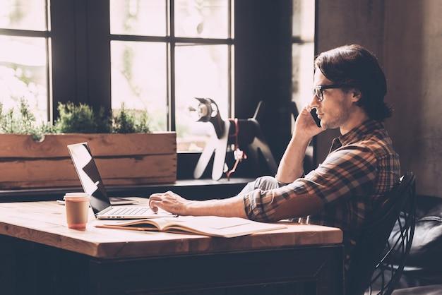 Concentrato sul lavoro. giovane allegro in abbigliamento casual che guarda il laptop e parla al telefono cellulare mentre è seduto vicino alla finestra in un ufficio creativo