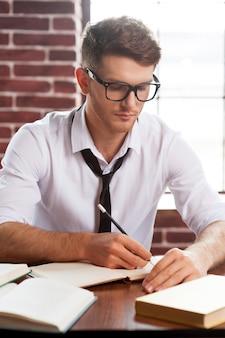 Concentrato sul lavoro. fiducioso giovane in camicia e cravatta che scrive qualcosa nel blocco note mentre è seduto al suo posto di lavoro