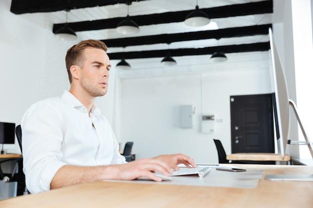 Giovane uomo d'affari concentrato seduto e lavorando con il computer sul posto di lavoro