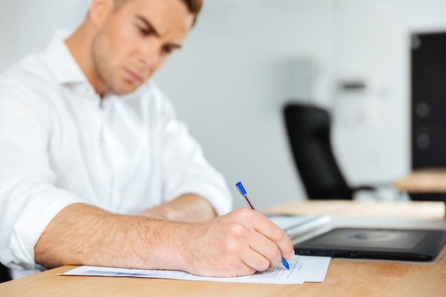 Giovane uomo d'affari concentrato seduto e scrivendo al tavolo
