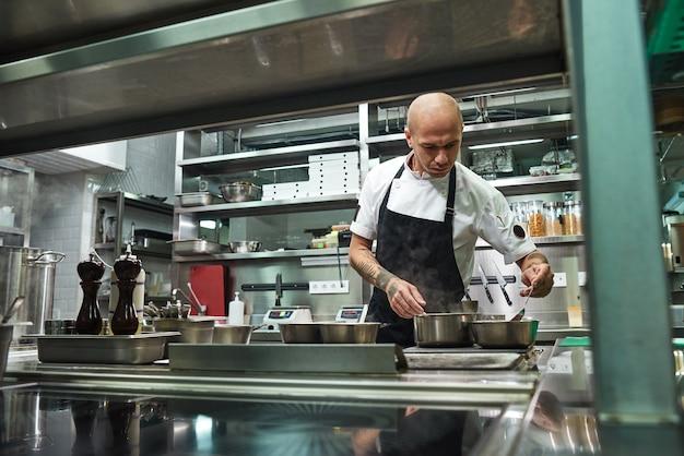 Il giovane chef concentrato in grembiule nero sta cucinando nella sua moderna cucina del ristorante