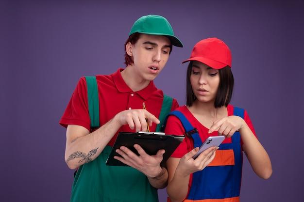 Concentrato giovane coppia in operaio edile uniforme e berretto che tiene matita e appunti che punta alla ragazza degli appunti che tiene e che indica al telefono cellulare entrambi guardando il telefono cellulare isolato