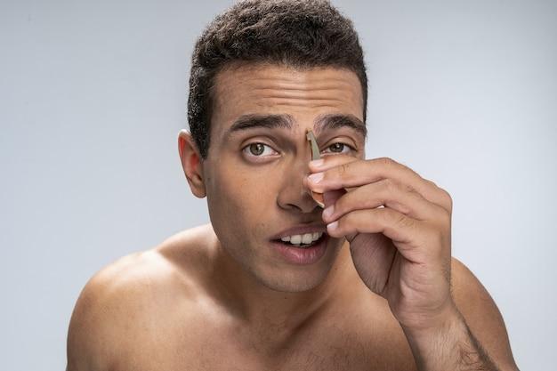 Giovane maschio concentrato che si strappa le sopracciglia folte