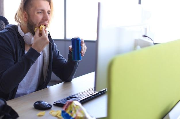 Giovane concentrato in abbigliamento casual che utilizza computer, riproduzione in streaming o video di procedure dettagliate e mangiare patatine.