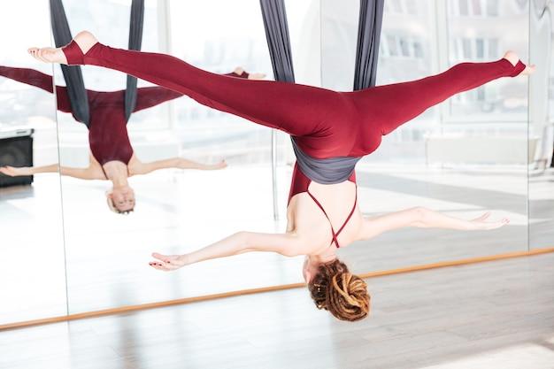 Giovane donna concentrata che fa posa di yoga antigravità usando un'amaca