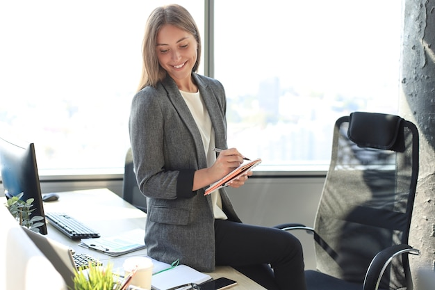 Giovane donna concentrata che scrive qualcosa mentre lavora in ufficio.