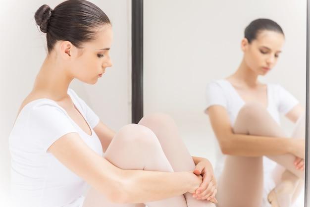 Concentrarsi prima dell'esibizione. bella giovane ballerina in tutù bianco seduta contro uno specchio