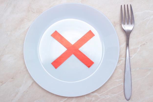 Concentrazione di rifiuto del cibo o nessun cibo. piatto con croce rossa.