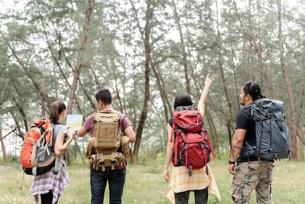 Concetto avventura ed escursionismo, gruppo di asiatici back-packers maschili e femminili sono quattro persone andate nei boschi per esplorare.