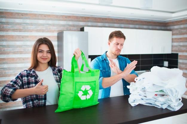 Concetto contro l'uso irragionevole di sacchetti di plastica. usa una borsa riutilizzabile - salva la natura dalle microplastiche. la giovane famiglia sceglie una borsa ecologica
