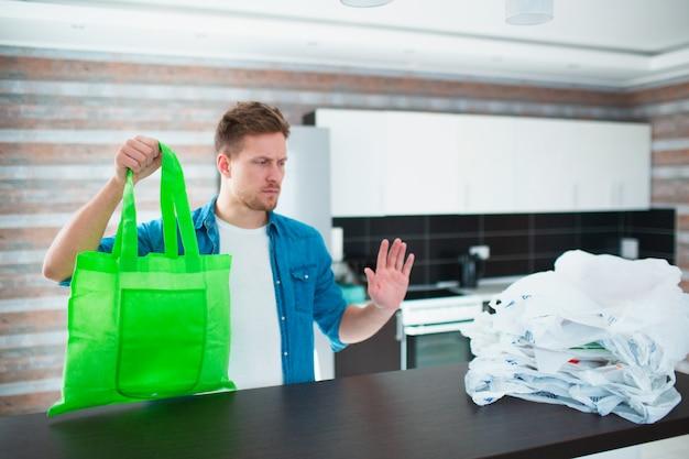 Concetto contro l'uso irragionevole di sacchetti di plastica. usa una borsa riutilizzabile - salva la natura dalle microplastiche. il giovane sceglie una borsa ecologica