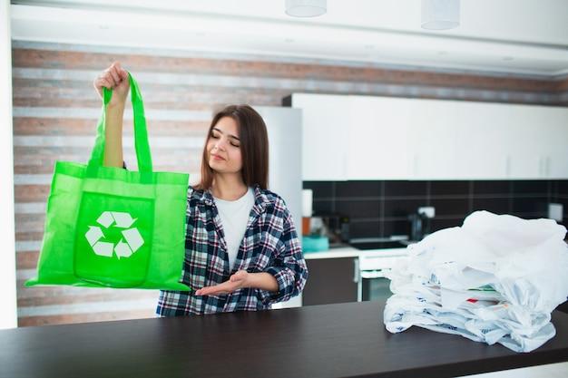 Concetto contro l'uso irragionevole di sacchetti di plastica. usa una borsa riutilizzabile - salva la natura dalle microplastiche. la giovane donna sceglie una borsa ecologica