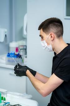 Concetto di anestesia, iniezione nelle mani dell'uomo. dentista maschio che tiene la siringa in mano, pronto a fare l'iniezione.