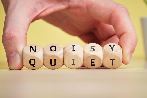 Concetto di antonimo rumoroso e silenzioso su blocchi di legno.