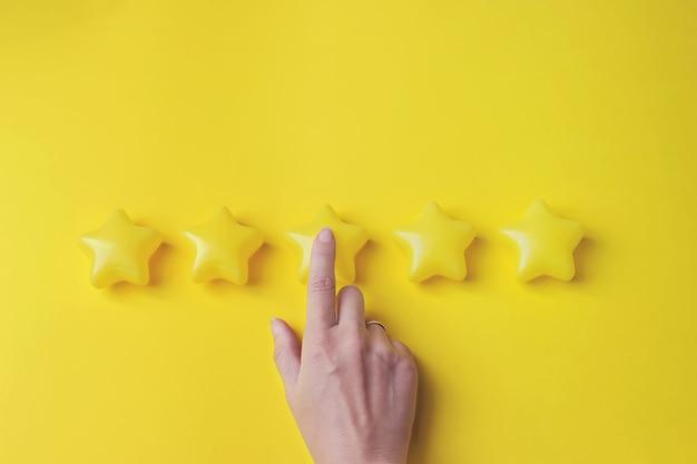 La valutazione del concetto. la mano che indica cinque stelle aumenta la valutazione dell'azienda, aumenta la valutazione