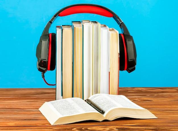 Concetto per audiolibri, pila di libri e cuffie.