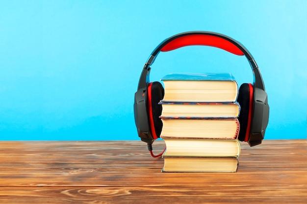 Concetto per audiolibri, pile di libri e cuffie su una parete blu. copia dello spazio.