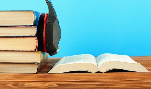 Concetto per audiolibri, pile di libri e cuffie. primo piano.