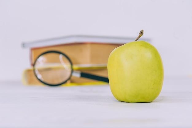 Concetto torna a scuola. mela verde con lente d'ingrandimento su uno spazio di libri.