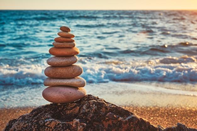 Concetto di equilibrio e armonia pila di pietre sulla spiaggia