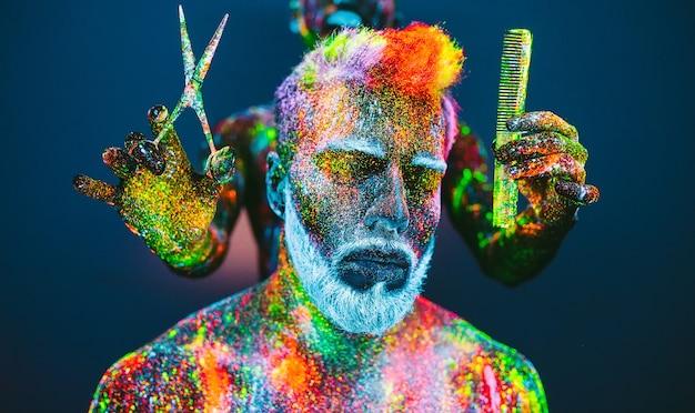 Concetto. un uomo con la barba nel barbiere. un elegante uomo con la barba viene rifilato nel barber shop. l'uomo è decorato con polvere ultravioletta.