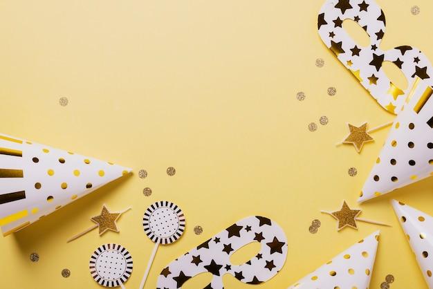 Concetto di festa di compleanno con cappelli da festa, maschere e candele su sfondo giallo. vista dall'alto in basso con copia spazio per il testo