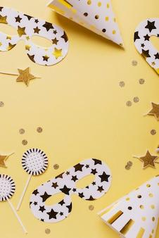 Concetto di festa di compleanno con cappelli da festa, maschere e candele su sfondo giallo. vista dall'alto in basso con copia spazio per il testo Foto Premium