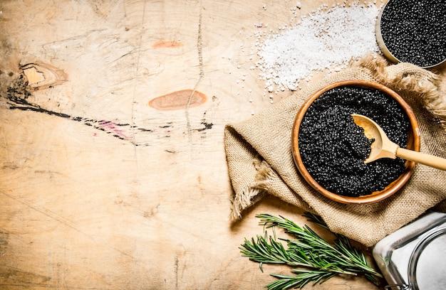 Il concetto di caviale nero caviale nero in una tazza con sale e rosmarino su un tavolo di legno