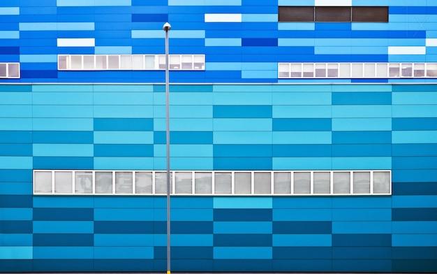 Concetto di un muro bianco e blu con e un palo del lampione