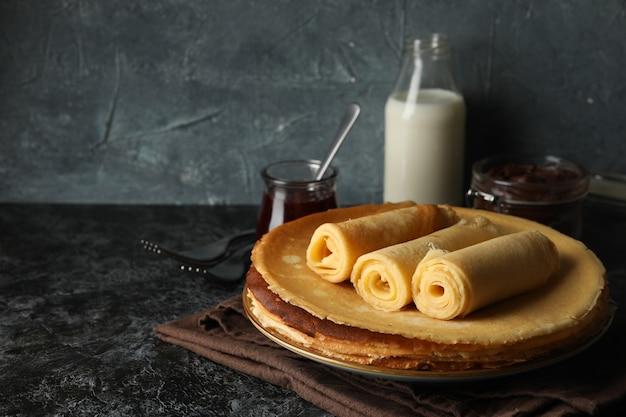 Concetto di colazione con crepes rotoli sul tavolo nero smokey