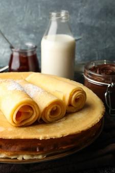 Concetto di colazione con crepes con zucchero in polvere e pasta di cioccolato