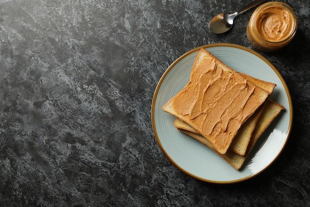 Concetto di colazione con pane tostato al burro di arachidi sul tavolo smokey nero