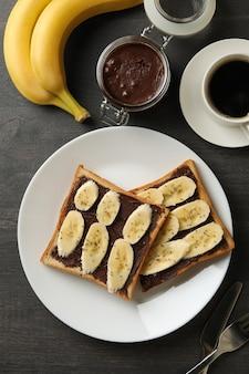 Concetto di colazione con pane tostato con banana su fondo in legno