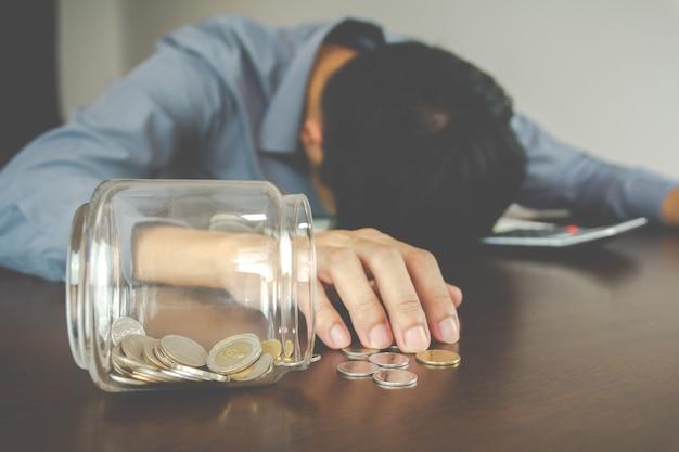 Concetto di perdita di affari. risparmio di denaro rotto. l'uomo d'affari è disperato e depresso perché non riesce a gestire i suoi soldi.
