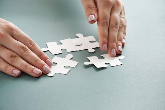Il concetto dell'affare, mani delle donne che tengono il puzzle bianco collega sul backgroud blu