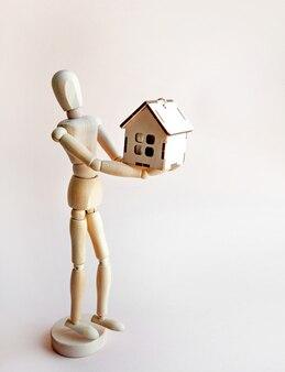 Il concetto di acquistare una casa una bambola di legno tiene una casa di legno su uno sfondo chiaro