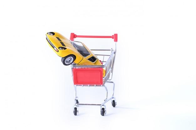 Concetto di acquisto di una nuova auto. automobile del giocattolo in cestino della spesa isolato