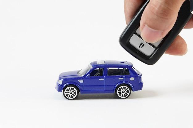 Concetto per auto e sicurezza, l'auto blu giocattolo e la chiave per la sicurezza.