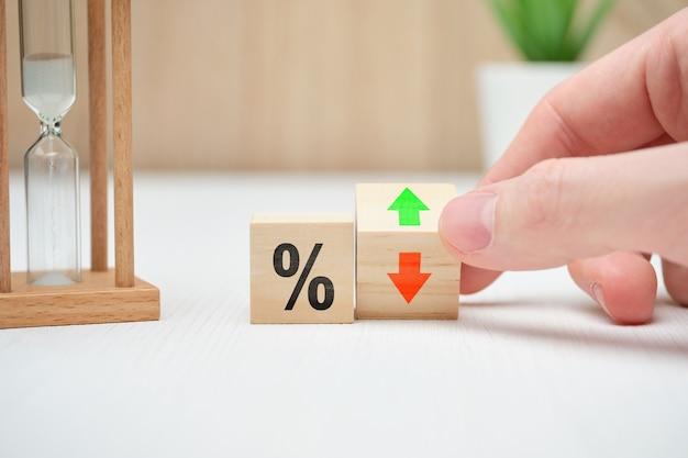 Il concetto di cambiare i tassi di interesse nelle banche che cadono e aumentano in modo astratto su blocchi di legno.