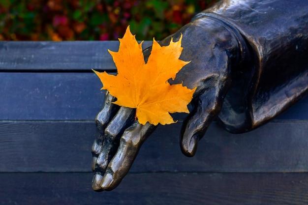 Concetto di cambiamento delle stagioni dell'anno, foglia d'acero gialla in una mano di ferro, primo piano.