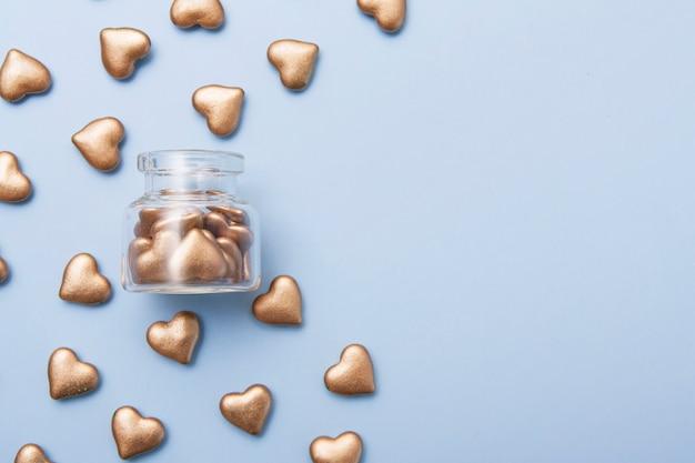 Concetto di carità, raccolta fondi e donazioni con cuori d'oro vicino e all'interno della bottiglia